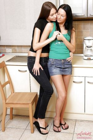 Two smoking hot teens enjoy lesbian strapon sex right in the kitchen
